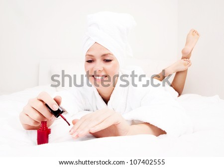 young beautiful woman applying red nail polish in bed at home - stock photo