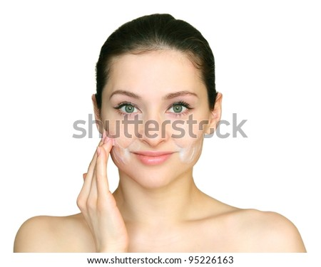 Young beautiful woman applying the cleansing foam on the face skin the hand isolated on white background. - stock photo