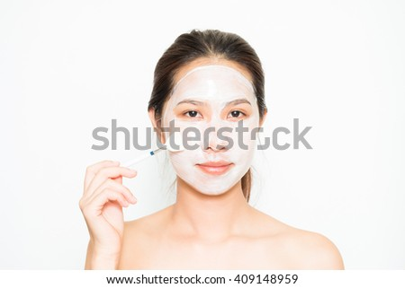 Young beautiful woman applying yogurt facial mask Skin care, beauty treatments on white background - stock photo