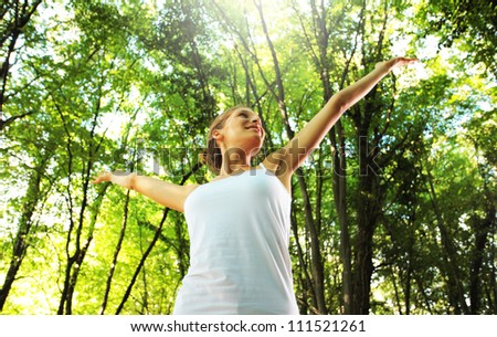 Young beautiful woman arms raised enjoying the nature in green forest - stock photo