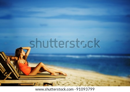 Young beautiful woman at beach on a lounge - stock photo