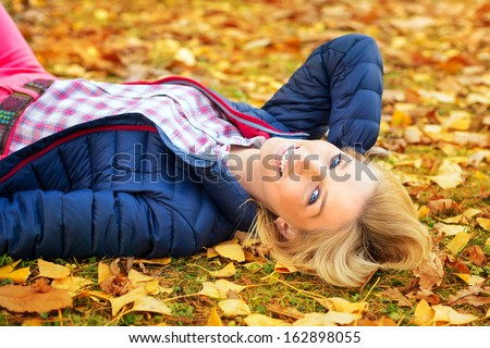Young beautiful woman at the autumnal park