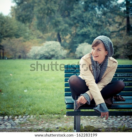 young beautiful woman at the park in autumn - stock photo