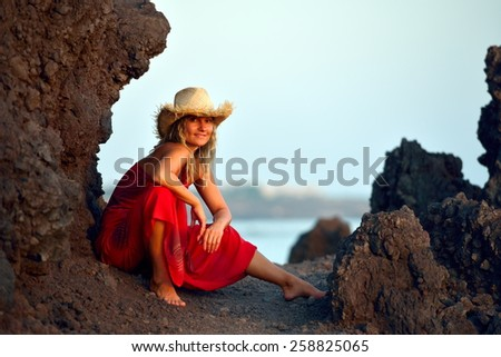young beautiful woman between black rocks on the beach in summer - stock photo