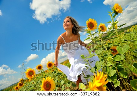 young beautiful woman between sunflowers - stock photo