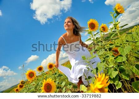 young beautiful woman between sunflowers - stock photo