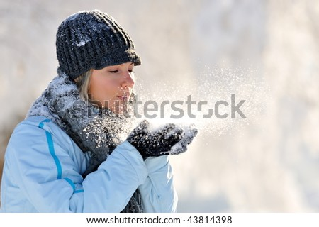 young beautiful woman blowing the snow