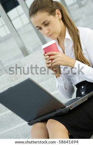 Young, beautiful woman business over coffee in the fresh air sitting on the stairs, office building, next to the laptop - stock photo