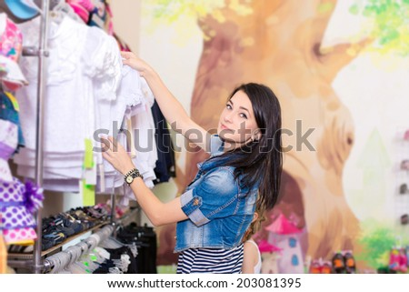 young beautiful woman buys clothes daughters - stock photo