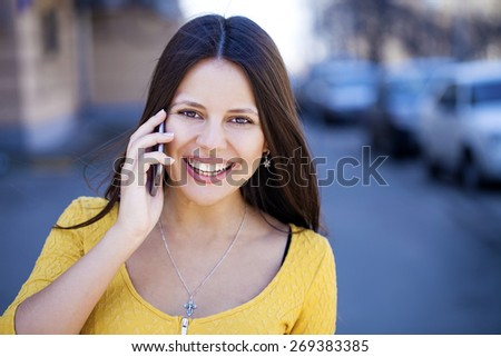 Young beautiful woman calls on his cell phone on the street - stock photo