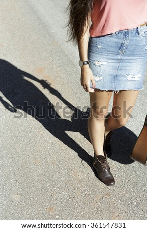 young beautiful woman carry an acoustic guitar along the road