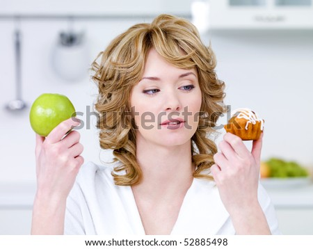 Young beautiful woman choose between sweet cake and green apple - in the kitchen - stock photo