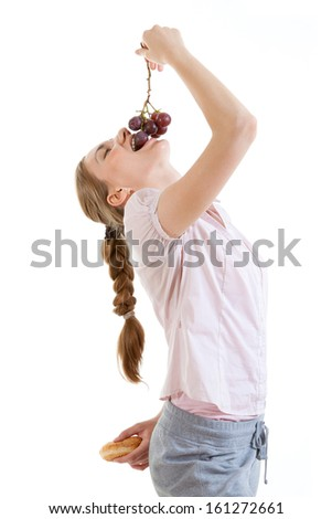 young beautiful woman choosing between burger and grapes - stock photo