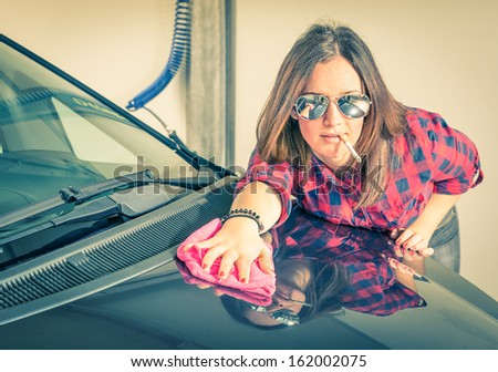 Young beautiful Woman cleaning her Car at Carwash - stock photo