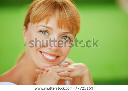 Young beautiful woman close up smiles, on green background.