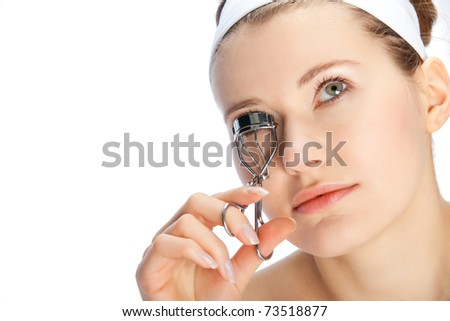 young beautiful woman cutting her eye lashes - stock photo