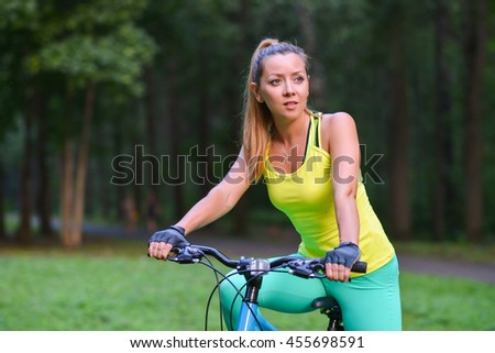 Young beautiful woman cycling on bicycle, summer park exercising - stock photo