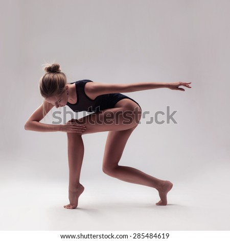 young beautiful woman dancer in black swimsuit posing on a light grey studio background
