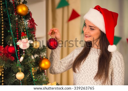Young beautiful woman decorates Christmas tree celebrating Christmas at home - stock photo