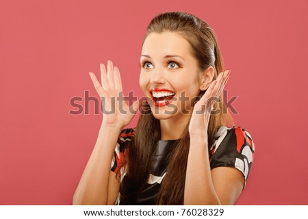Young beautiful woman delightfully plants hands and is surprised, on red background. - stock photo