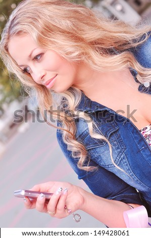 Young beautiful woman dialing phone number outdoors - stock photo