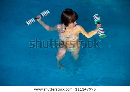 Young beautiful woman doing aqua gym exercise with water dumbbell in a swimming pool