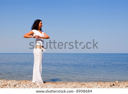Young beautiful woman doing fitness exercises in the sea