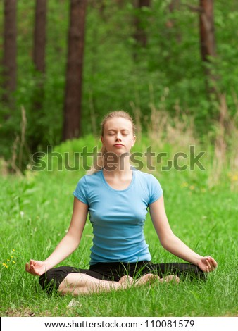 Young beautiful woman doing yoga meditation exercise in forest outdoors - stock photo