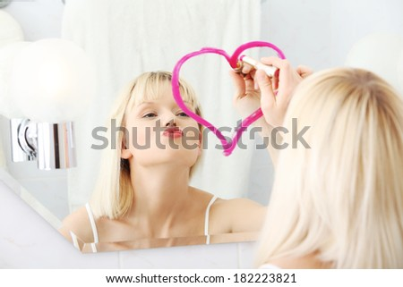Young beautiful woman drawing big heart on mirror in bathroom.  - stock photo