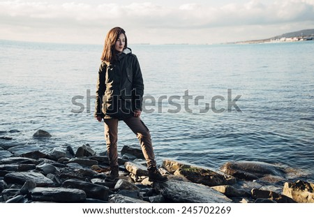 Young beautiful woman dressed in a coat and cargo pants standing on rocky shore near the sea