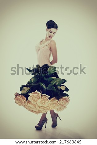 Young beautiful woman dressed in elegant dress of fresh rose flowers, image toned. - stock photo
