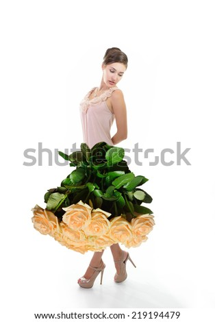 Young beautiful woman dressed in elegant dress of fresh rose flowers, isolated on white - stock photo