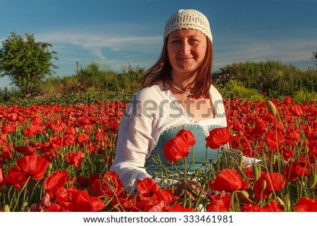 Young beautiful woman dressed in folklore style in the midst of poppy field