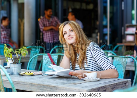 Young beautiful woman drinking coffee and reading book in an outdoor cafe in Hamburg, Germany.
