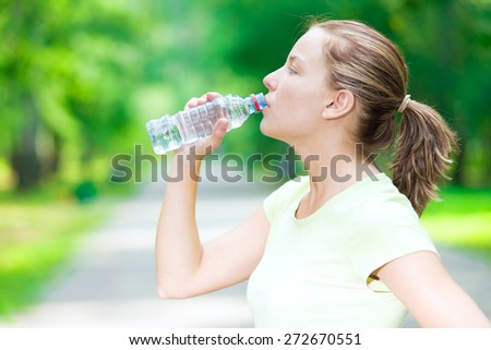 Young beautiful woman drinking cold mineral water from a bottle  after sport fitness exercise at green summer park - stock photo