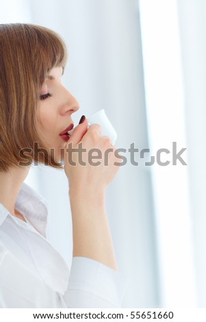 Young beautiful woman drinking fresh coffee - stock photo