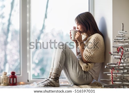 Young beautiful woman drinking hot coffee sitting on window sill in christmas decorated home. Holiday concept