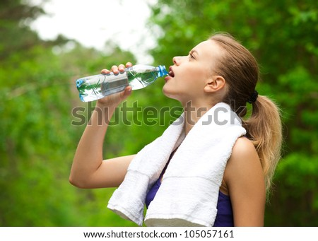 Young beautiful woman drinking water after fitness exercise outdoors - stock photo