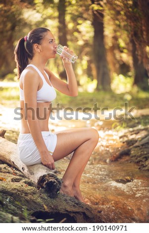 Young beautiful woman drinking water in forest
