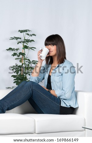 Young, beautiful woman drinks a cup of coffee while sitting on the couch - stock photo