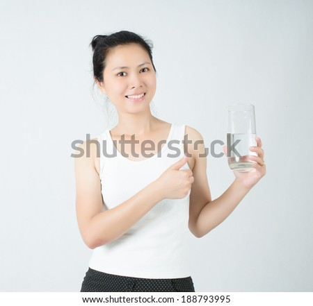 young beautiful woman drinks water from a glass and showing thumbs up - stock photo