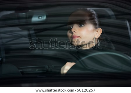 young beautiful woman driving a car and smiling - stock photo