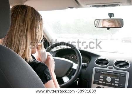 Young beautiful woman driving car and eating fast food - rear view - stock photo