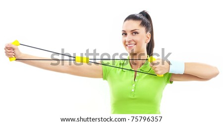 Young beautiful woman during fitness with expander - stock photo