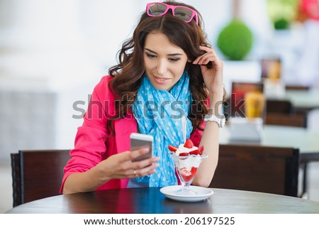 young beautiful woman eating a dessert. Image of young female reading sms on the phone in cafe. Cute young woman in cafe restaurant with phone - stock photo