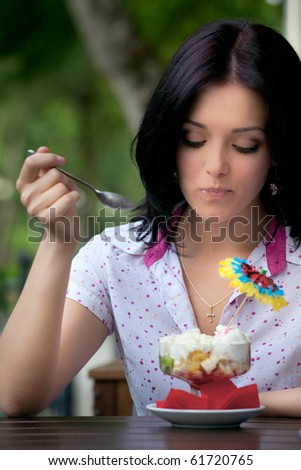 young beautiful woman eating an ice cream in cafe - stock photo