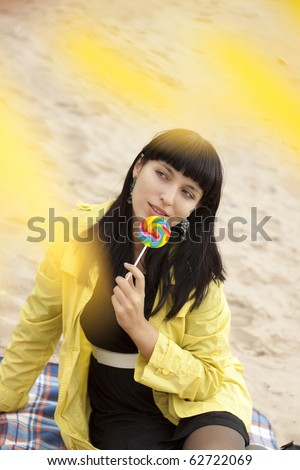 Young beautiful woman eating candy - stock photo