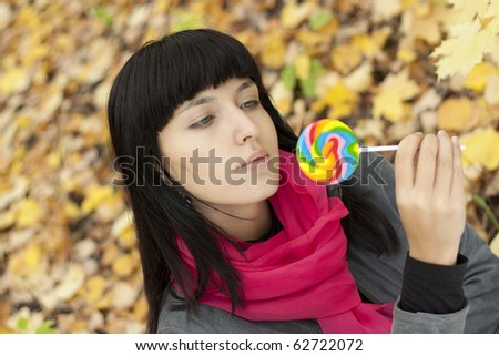 Young beautiful woman eating candy.