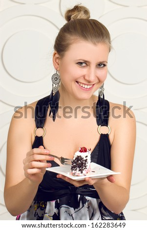 Young beautiful woman eating  chocolate cake. - stock photo