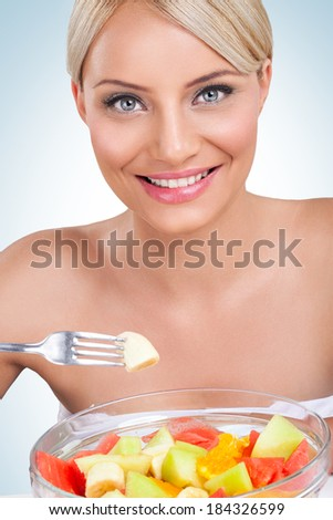 Young beautiful woman eating healthy fruit salad  - stock photo